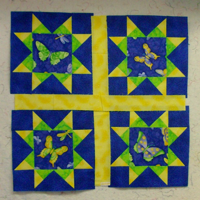 Four quilt blocks together of the Arm Star Quilt Block outlined with a yellow boarder.