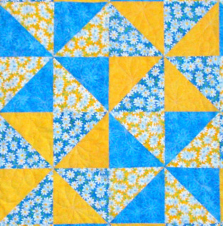 Four pinwheel quilt blocks sewn together.