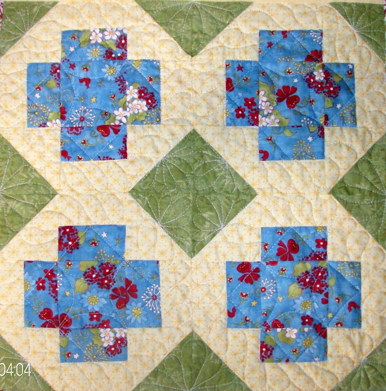 Four quilt squares sewn together of the Greek Cross block.
